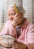 梳她的头发的老微笑的妇女 库存图片