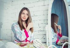 梳她的头发的青少年的女孩 库存图片