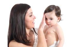 梳她的婴孩的可爱的母亲 免版税库存图片