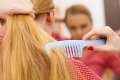 梳她长的头发的妇女在卫生间里 免版税图库摄影