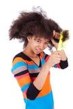 梳她非洲的头发的黑人非裔美国人的十几岁的女孩 免版税库存照片