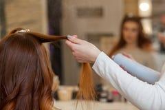 梳她他的客户的长,红色头发的美发师和洒在美容院的喷发剂 库存照片