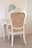 梳妆台和白色椅子在旅馆客房 免版税库存照片
