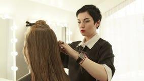 梳妇女理发前面镜子的女性美发师长的头发在美容院 关闭haircutter分开头发 影视素材