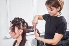 梳客户在沙龙的头发梳妆台特写镜头` s头发 免版税库存照片
