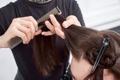 梳客户在沙龙的美发师特写镜头` s头发 免版税库存图片