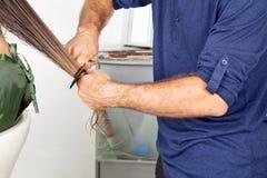 梳客户的湿头发的美发师 免版税库存图片