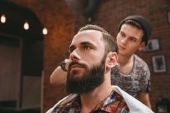 梳客户的头发的有胡子的现代理发师在理发店 免版税库存照片