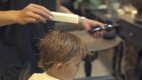 梳小男孩的头发的美发师在发型沙龙的孩子理发前 与梳子的儿童理发切开的 股票视频