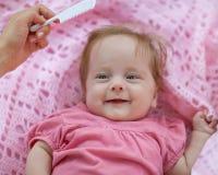 梳新出生的女孩的母亲。 免版税库存图片