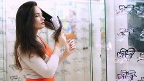梳有一把圆的梳子的美丽的妇女黑暗的长的头发 股票录像