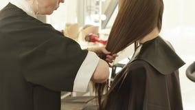 梳湿头发的美发师在理发沙龙的女性理发期间 关闭做女性理发的美发师  股票录像