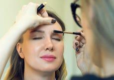 梳眼眉的化妆师 库存图片