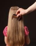 梳美丽的长的头发的女性手 免版税库存图片