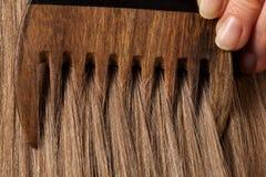梳美丽的长的头发的女性手 免版税图库摄影