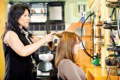 梳顾客的头发 图库摄影