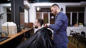 梳头发的大师侧视图对理发店的男性顾客 股票录像