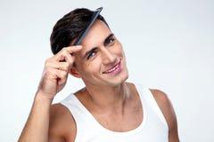 梳他的头发的愉快的人 免版税库存图片