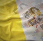 梵蒂冈五颜六色的挥动的国旗欧元金钱钞票背景的 库存照片