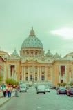 梵蒂冈,意大利- 2015年6月13日:圣伯多禄圆顶在街道结束时,对梵蒂冈国家的门 长和老街道 库存照片