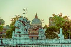 梵蒂冈,意大利- 2015年6月13日:圣伯多禄圆顶远的看法与scultures的在突破口和公众照明设备,日落是 免版税库存照片