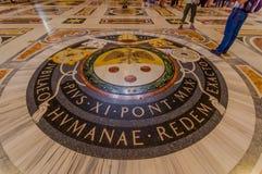 梵蒂冈,意大利- 2015年6月13日:在地板上的梵蒂冈封印在圣伯多禄大教堂入口  免版税库存图片