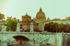 梵蒂冈,意大利- 2015年6月13日:对圣伯多禄圆顶的远的看法在梵蒂冈,在突破口和日落下的graffittis点燃 免版税库存照片