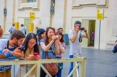 梵蒂冈,意大利- 2015年6月13日:拍在大教堂之外的未认出的人民照片在梵蒂冈,圣彼得 免版税库存照片