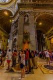 梵蒂冈,意大利- 2015年6月13日:看和拍在圣伯多禄大教堂里面的游人照片Vaticano,在罗马教皇后 图库摄影