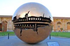 梵蒂冈2017年6月13日:梵蒂冈,由意大利雕刻家阿纳尔多Pomodoro意大利的一个铜雕塑的附上的法院 免版税图库摄影