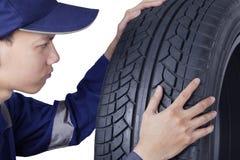 检查一个新的汽车轮胎的技工 免版税库存照片