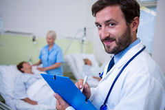 检查一个医疗报告的微笑的医生画象 免版税库存图片