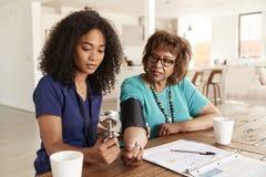 检查一名资深妇女的血压的女性医疗保健工作者在一次家庭参观期间 免版税库存照片
