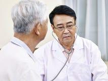 检查一名资深患者的亚裔医生 库存照片