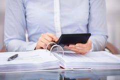 检查一张发货票的买卖人在办公室 免版税库存照片