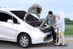 检查一辆残破的汽车的回教家庭 免版税库存照片