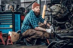 检查一辆汽车的引擎的在车库的Mechanicl 免版税库存图片