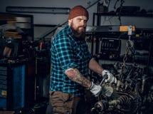检查一辆汽车的引擎的在车库的Mechanicl 库存图片