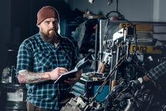 检查一辆汽车的引擎的在车库的Mechanicl 库存照片