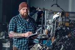 检查一辆汽车的引擎的在车库的Mechanicl 免版税库存照片