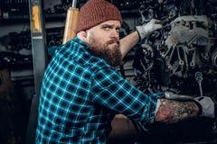 检查一辆汽车的引擎的在车库的Mechanicl 免版税图库摄影