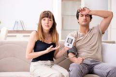 检查丈夫的血压的妻子 图库摄影
