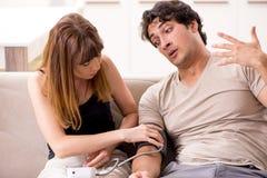 检查丈夫的血压的妻子 免版税库存照片