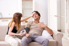 检查丈夫的血压的妻子 免版税库存图片