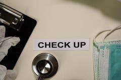 检查与启发和医疗保健/医疗概念在书桌背景 免版税库存图片