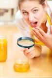 检查与放大镜的妇女蜂蜜 免版税库存照片