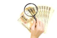 检查与放大镜的金钱日元日本在白色背景 库存照片