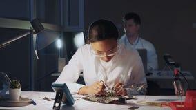 检查主板与多用电表测试器和其他电子构想的非裔美国人的电子工程师在实验室