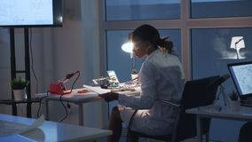 检查主板的后面观点的女性电子工程师与多用电表测试器