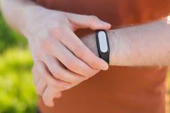 检查他的在聪明的手表跟踪仪的运动员脉冲 库存图片